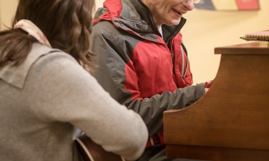 A SSC music therapist with an elderly student during a therapy session, image by Jack Foley